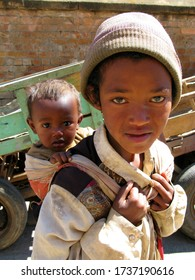 ANTSIRABE, MADAGASCAR, octobre 5, 2008: Young boy holding his little brother behind his back. Cart in the background.
