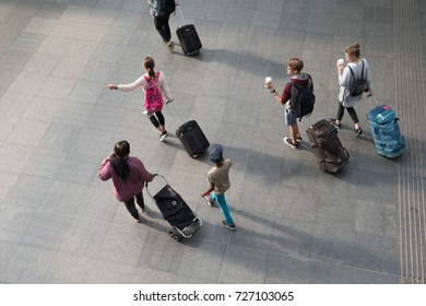 Antwerp, Belgium - 13 August 2017: Bird's eye view of a family walking through the train station at Antwerp pulling their suitcases and luggage behind them. Man carries paper coffee cup.