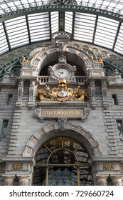 Antwerp, Belgium - 13 August 2017:Antwerpen Centraal railway station in Antwerp Belgium. Clock tower at the upper level.Ornate clock with Belgium crest, clock reads 11:37 am.Gilded clock in train hall