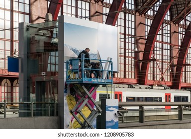 Antwerp, Belgium - 2018-10-01: High above a busy station hall, on a highworker scaffold platform on wheels, two men are busy placing a huge advertisement poster on the outside hoistway of the lift.
