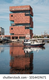 Antwerp, Belgium - 22 July 2017: Boat sailing out of Willemdok, with modern MAS museum in the background.
