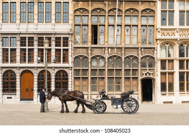 Antwerp, Belgium - April 14, 2010: A traditional horse drawn buggy and driver in front of the guildhouses at Grote Markt waiting for tourists to tour the famous sights in the old city