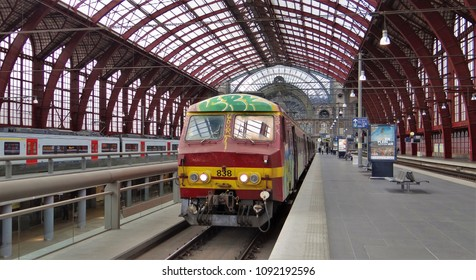 Antwerp / Belgium - April 30 2016: An old red and yellow NMBS passenger train on the central railway station (cathedral) of Antwerp with the beautiful red roof.