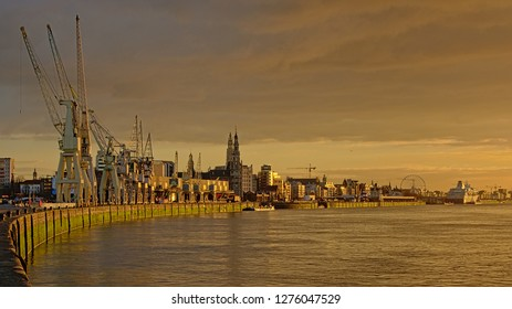 ANTWERP, BELGIUM, DECEMBER 11, 2018, Quay along river Scheldt in the port, with old industrial cranes of the collection of MAS museum and the city in the background. Antwerp, 11 December 2018