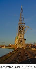 ANTWERP, BELGIUM, DECEMBER 11, 2018, Quays of the harbor of Antwerp, with old industrial cranes in warm sunset light. Antwerp, 11 December 2018