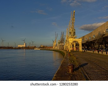 ANTWERP, BELGIUM, DECEMBER 11, 2018, Quay along river Scheldt with old industrial cranes, part of the collection of MAS museum and harbor buildings and wind turbines. Antwerp, 11 December 2018