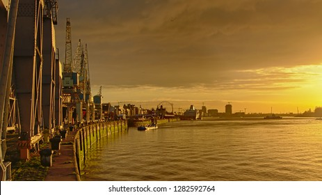ANTWERP, BELGIUM, DECEMBER 11, 2018, Quay along river Scheldt  with old industrial cranes, part of the collection of MAS museum and the city and cathedral in the background. Antwerp, 11 December 2018