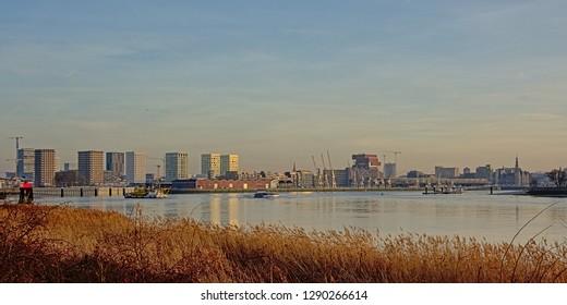 ANTWERP, BELGIUM, DECEMBER 26, 2018, skyline from across river Scheldt, with MAS museum, old industrial cranes and new residential skyscrapers in warm evening light, Antwerp, 26 December 2018