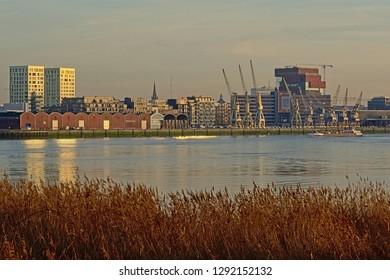 ANTWERP, BELGIUM, DECEMBER 26, 2018, skyline from across river Scheldt, with MAS museum, old industrial cranes and new residential skyscrapers in warm evening light. Antwerp, 26 December 2018