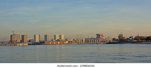 ANTWERP, BELGIUM, DECEMBER 26, 2018, skyline from across river Scheldt, with MAS museum, old industrial cranes and new residential skyscrapers in warm evening light . Antwerp, 26 December 2018