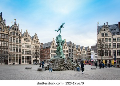 ANTWERP, BELGIUM - FEBRUARY 21, 2019: A group of tourists taking photos around the Brabo Fountain at Grote Markt square in the center of Antwerp with the views of traditional houses in the backgroud.