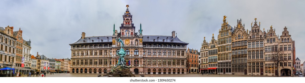 Antwerp, Belgium - January 18, 2015: Cityscape panorama with Brabo fountain in front of City Hall or Stadhuis and traditional brick gothic medieval guildhouses on Grote Markt square
