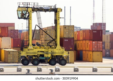 ANTWERP, BELGIUM - JUL 9, 2013: Straddle carrier moving shipping containers in the Port of Antwerp.