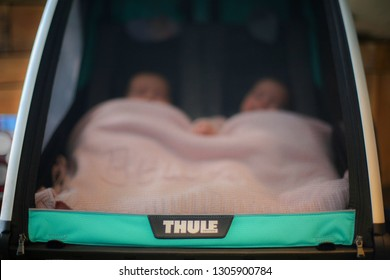 ANTWERP, BELGIUM - JULY 27TH 2018: Cute twin babies sleeping inside a closed, double baby stroller, made by Thule. Thule is a Swedish company that produces transportation gear. Illustrative editorial.