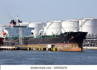 ANTWERP, BELGIUM - JULY 9: Oil tanker near oil silos in the Port of Antwerp July 9,2013 in Antwerp, Belgium. The Port of Antwerp is the Europe's second largest sea port after Rotterdam.
