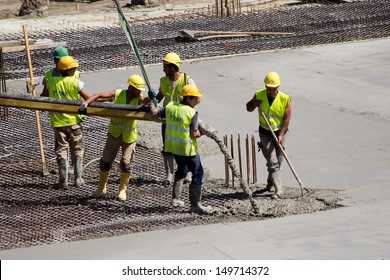 ANTWERP, BELGIUM - JULY 9: Workers pouring concrete for the bases of the new Antwerp Port Authority HQ on July 9, 2013 in Antwerp, Belgium. The new building will be build over a monumental building.