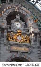 """Antwerp, Belgium - June 10, 2018:  Clock and """"Antwerpen"""" lettering inside Antwerpen-Centraal (Antwerp Central) railway station in the Belgian city of Antwerp"""