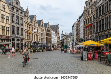 Antwerp / Belgium - June 23 2019: People walking through shops and others sit at street cafes in the centre of Antwerp in Belgium.