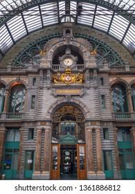 """Antwerp, Belgium – June 9, 2018: Clock and """"Antwerpen"""" lettering inside Antwerpen-Centraal (Antwerp Central) railway station in the Belgian city of Antwerp"""