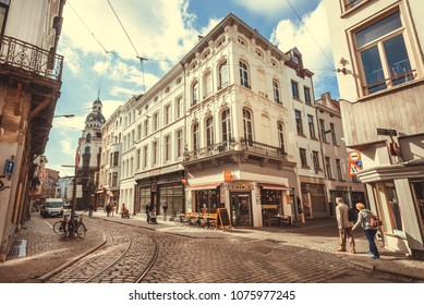 ANTWERP, BELGIUM - MAR 30: Bright corner of streets in historical city with cobbled stones, restaurants and walking seniors on March 30, 2018. More than 1,200,000 people lives in Antwerp