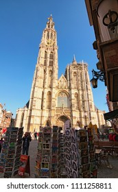 Antwerp, Belgium – MAY 02, 2018: Amazing Cathedral of Our Lady. Tower of the cathedral is the highest in the Benelux. Several racks with different souvenir's postcards in the foreground.