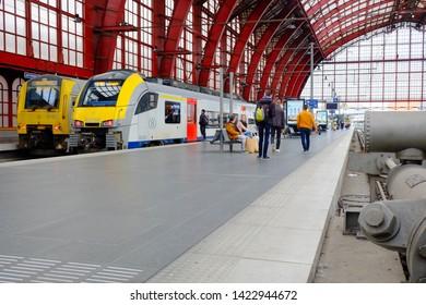 Antwerp, Belgium, May 2019,  Rear view of people waiting and walking towards metro train at Antwerp Central Station, Belgian. Antwerp Central the main train station in the Belgian city of Antwerp.