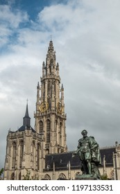Antwerp, Belgium - September 24, 2018: Peter Paul Rubens bronze statue with towers of Onze-Lieve-Vrouwe Cathedral of Our Lady in back under white cloudy sky.