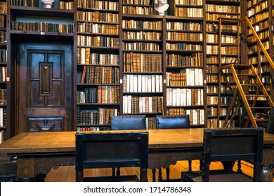 ANTWERP, BELGIUM: Volumes of 17th century books and 18th on bookshelves of an old library, antique book collection on March 30, 2018. Part of historical house of the Plantin-Moretus printing Museum