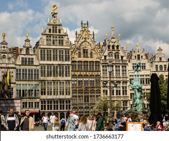 Antwerp, Flanders, Belgium. August 2019. On a beautiful sunny day the facades of the guild houses in the town hall square spice for beauty. People enjoy the beautiful day.