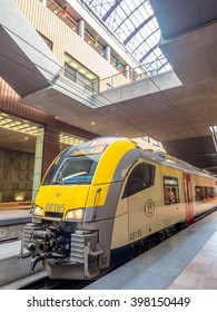 ANTWERP - OCTOBER 1: Scene in Antwerp train station on platform with yellow colorful train in Belgium, was taken on October 1, 2015.