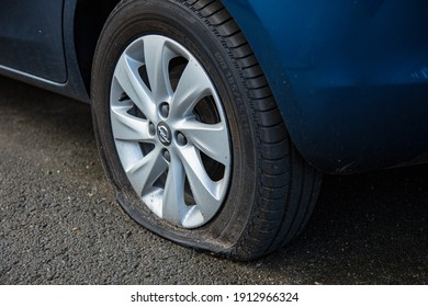 Antwerpen, Belgium - February 5, 2021: Broken car wheel, car is on the side of the road, close-up on a tire