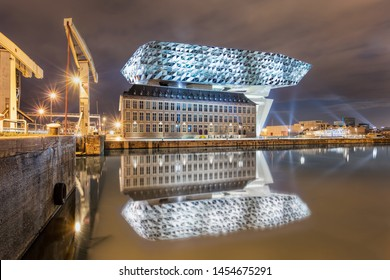 ANTWERP-JUNE 15, 2019. Port House Antwerp at nighttime. Zaha Hadid Architects added a glass extension to a renovated fire station. With total of 12,800 square meters headquarters houses a 500 staff.