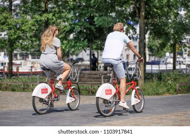 ANTWERP-MAY 21, 2018. Young couple on Velo rental bikes, a form of public transport, easily to combine with train, tram and bus. The first half hour of each ride is included in the registration fee.