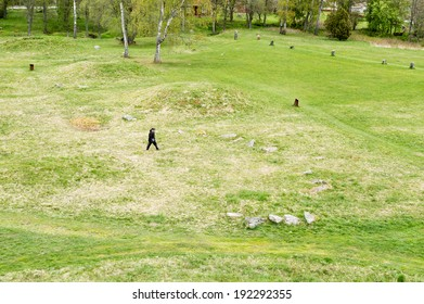 ANUNDSHOG, SWEDEN - MAY 06, 2014: People visiting the burial field with stone ships at and burial mounds.