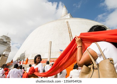 ANURADHAPURA, SRI LANKA - 21 Feb 2016: A procession of people dressed in white wraps a 366m orange cloth around the Ruwanwelisaya stupa for the Full Moon Hindu ceremony in Anuradhapura, Sri Lanka.