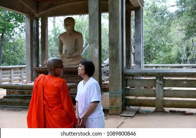 Anuradhapura, Sri Lanka April 5, 2018 A female Buddhist monk and a devotee at Samadhi Buddha statue in Mahamevuna Park Anuradhapura, Sri Lanka on April 5, 2018