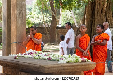 Anuradhapura - Sri  Lanka - Circa 2013 - Young monks pay their respect to the image of the Samadhi Buddha with prayers and offerings.