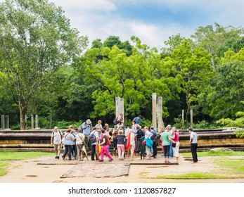 Anuradhapura, Sri Lanka - November 10, 2017:  A group of western tourists looking at the famous moonstone of the monastic residential complex, Anuradhapura ancient city, Sri Lanka.