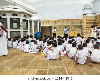 Anuradhapura, Sri Lanka - November 11, 2017:  Young Sri Lankan pupils in white uniform sitting and listening to the briefing about Ruwanwelisaya stupa in the Anuradhapura ancient city, Sri Lanka.