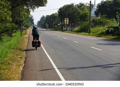 ANURADHAPURA,SRI LANKA - JANUARY 262018:woman cycling the main road on January 26,2018 in Anuradhapura,Sri Lanka