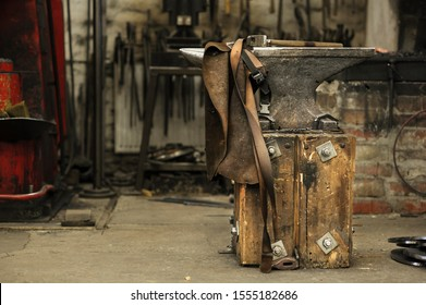 Anvil, hammer and leather apron in smithy