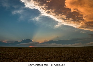 The anvil of a Texas thunderstorm is illuminated by the light of the setting sun