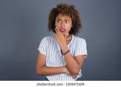 Anxiety - a conceptual image of a beautiful young African American woman covering her mouth with her hands and standing indoors. Scared from something or someone bitting nails