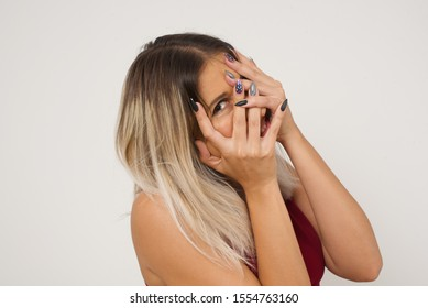 Anxiety - a conceptual image of a beautiful young caucasian woman covering her face with her hands and peering out with one eye between her fingers standing indoors. Scared from something or someone.