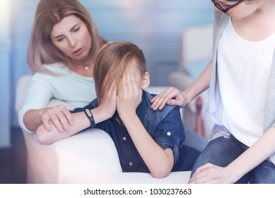 Anxiety and depression. Worried mother and professional psychotherapist trying to calm a teenage boy down while hovering his face and crying.