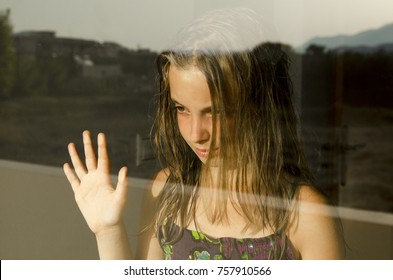 Anxiety and sad child girl looking out the window and lean her palm hand on the glass. Puberty pensive little girl. Nature reflection on glass.