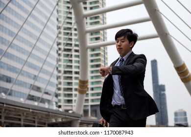 Anxious Asian businessman run and look at watch to check time on city walk in rush hour. Young man late for train transportation, work, meeting. Office life and business competition.