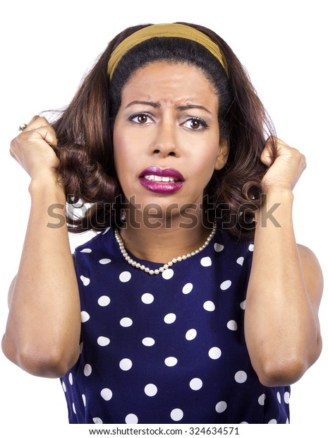 Anxious black female wearing retro fashion style polka dot dress.  She is fed up and pulling her hair.