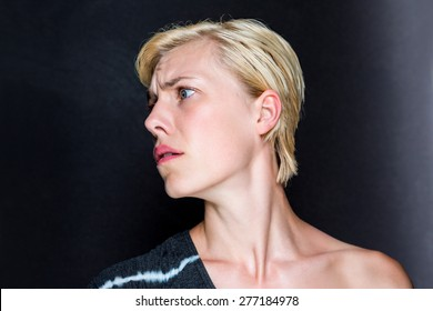Anxious blonde woman on black background