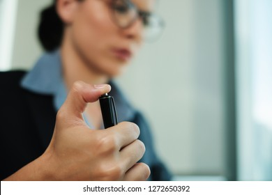 An anxious, bored business woman professional clicks on her pen button repeatedly while working at the office. Concept of boredom stress, impatience or irritation. Nervous Tics and Work related stress
